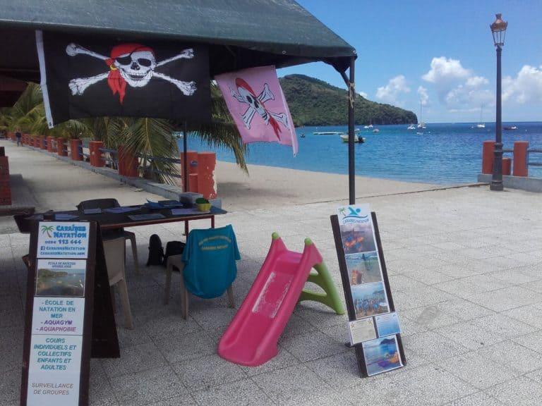 Matériels, décorations, banderoles pour l'emplacement de l'accueil des les inscriptions au forum des Anses d'Arlet et vue mer en arrière plan